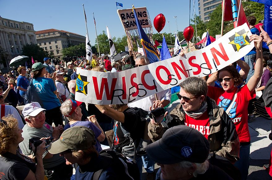 A group from Wisconsin marches to a stage where hundreds of protesters, upset about a variety of issues from the ongoing wars in Afghanistan and Iraq to corporate greed and jobs, gather at Freedom Plaza before marching to the White House, Chamber of Commerce and along K Street in NW Washington, DC, October 6,  2011. (Andrew Harnik / The Washington Times)