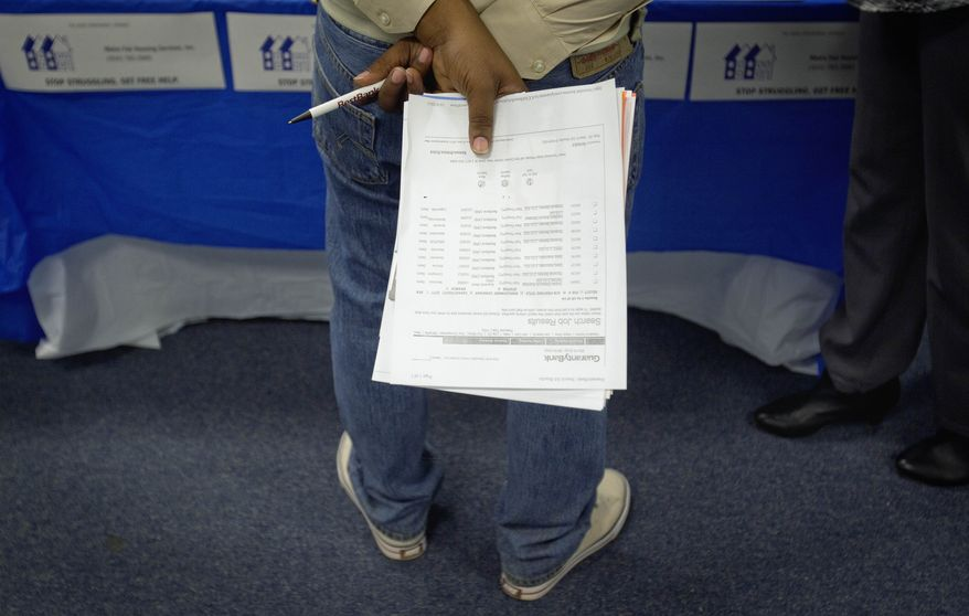 A job seeker holds a list of employment openings while talking with a recruiter during a job fair at a Goodwill store in Atlanta on Tuesday, Oct. 4, 2011. (AP Photo/David Goldman)