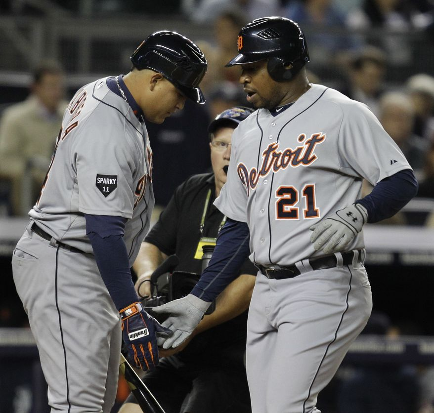 Detroit Tigers' Delmon Young, right, is congratulated by teammate Miguel Cabrera after hitting a home run in the first inning in Game 5 of baseball's American League division series against the New York Yankees Thursday, Oct. 6, 2011 in New York. (AP Photo/Kathy Willens)