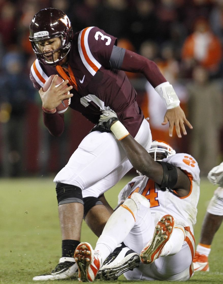 Virginia Tech quarterback Logan Thomas (3) gets hauled down by Clemson defensive tackle Rennie Moore (94) during the second half of an NCAA college football game at Lane Stadium in Blacksburg, Va., Saturday, Oct. 1, 2011. Clemson won 23-3. (AP Photo/Steve Helber)
