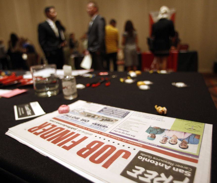 **FILE** Job seekers and vendors attend a job fair on Oct. 4, 2011, in San Antonio. (Associated Press)