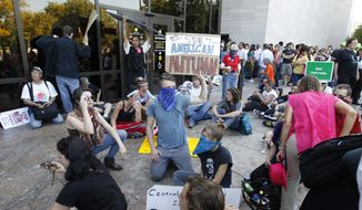 "A group of demonstrators sit outside the entrance to the National Air and Space Museum in Washington after police pepper-sprayed a group of protestors trying to get into the museum Saturday, Oct. 8,  2011, as part of Occupy DC activities in Washington. One protester held a sign with the writing, ""The American Autumn"", a takeoff reference to the Arab Spring uprisings in the Middle East. (AP Photo/Jose Luis Magana)"