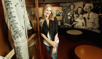 """Holly Williams, granddaughter of Hank Williams, stands in the Williams family exhibit at the Country Music Hall of Fame and Museum in Nashville, Tenn. Miss Williams is one of the performers on """"The Lost Notebooks of Hank Williams."""" Behind her is a photo of Hank Williams and his family."""
