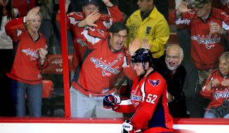 Washington Capitals defenseman Mike Green (52) is cheered on by fans after his game-winning goal against the Carolina Hurricanes during the overtime period of an NHL hockey game, Saturday, Oct. 8, 2011, in Washington. The Capitals won 4-3 in overtime. (AP Photo/Nick Wass)