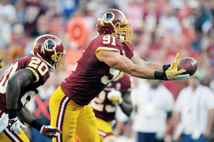 Washington Redskins linebacker Ryan Kerrigan (91) grabs a batted down pass by New York Giants quarterback Eli Manning and carries it in for a touchdown during the second half of an NFL football game in Landover, Md., on Sunday, Sept. 11, 2011. (AP Photo/Cliff Owen)