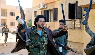 Revolutionary fighters celebrate inside Sirte, Libya, on Sunday, Oct. 9, 2011. Rebel forces have besieged the city since mid-September and are facing fierce resistance from loyalists while moving inside the hometown of ousted leader Col. Moammar Gadhafi. (Associated Press)