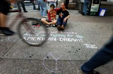 Lauren Bieber and Mike Mull, both from Philadelphia, sit next to a haiku they wrote on the sidewalk near City Hall on Sunday in Philadelphia. Organizers of what is being called Occupy Philadelphia say the demonstration is meant to be a stand against corporate greed. (Associated Press)