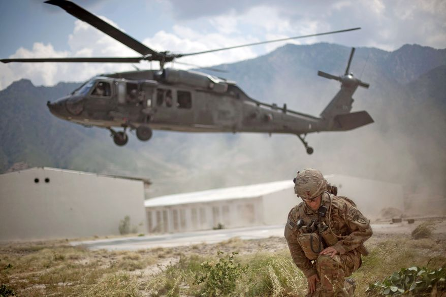 ** FILE ** Capt. Michael Kolton, 28, of Fairfax Station, Va., turns from the rotor wash of a Blackhawk helicopter at the Shigal district center in Kunar province, Afghanistan. (Associated Press)