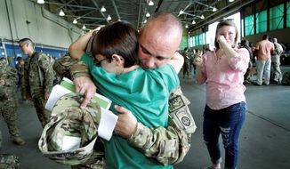 Army 1st Sgt. Jason Friedly of New Bethlehem, Pa., hugs his son, Tanner, 11, as daughter, Lakyn, looks on during 82nd Airborne Combat Aviation Brigade deployment to Afghanistan from Fort Bragg, N.C., earlier this month. (Associated Press)