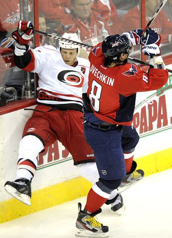 Carolina Hurricanes defenseman Tim Gleason  is checked into the boards by Washington Capitals left wing Alex Ovechkin during the first period Saturday, Oct. 8, 2011, in Washington. (AP Photo/Nick Wass)