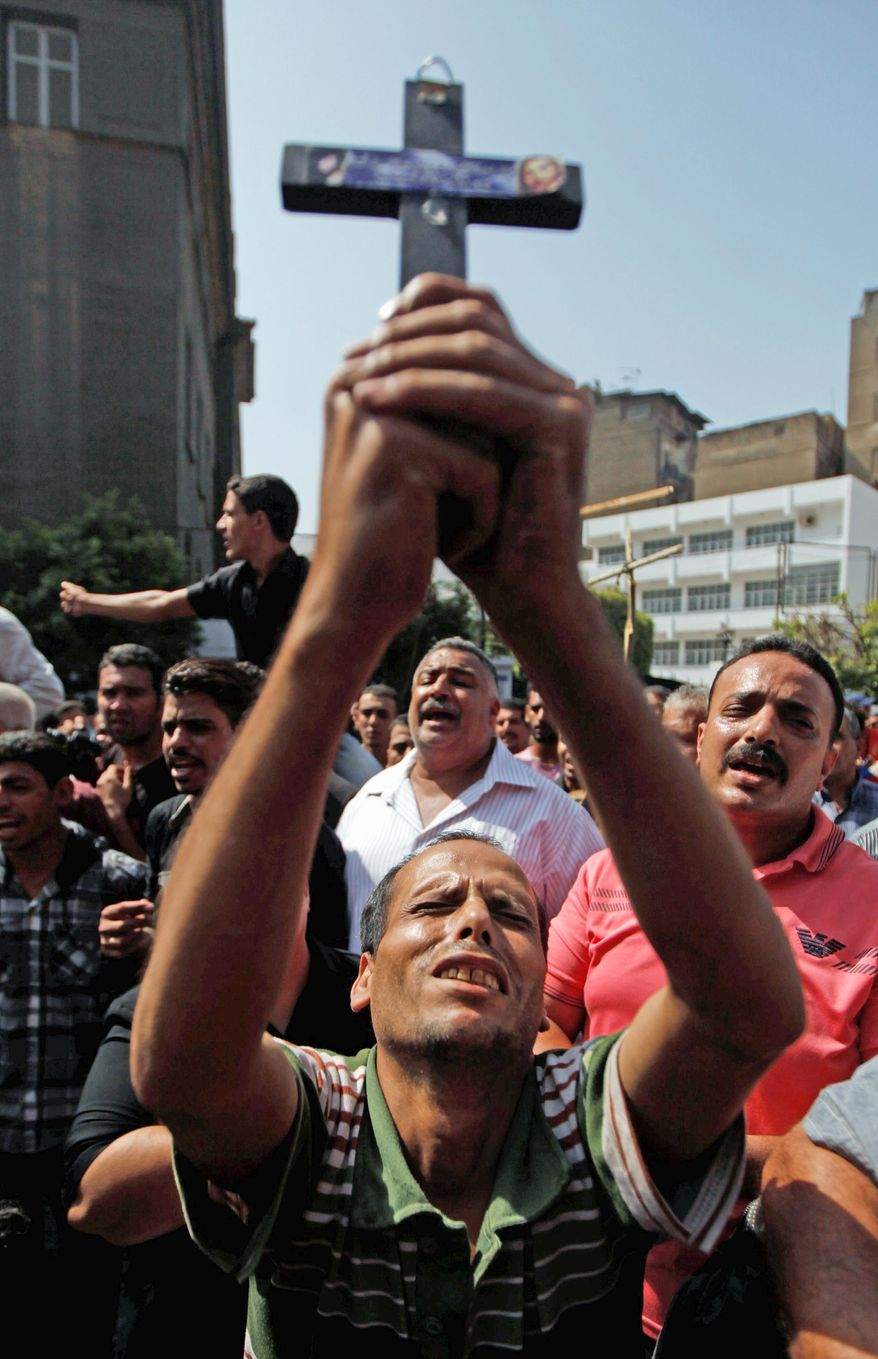 An Egyptian relative of one of the Copts killed during clashes with the Egyptian army late Sunday holds a cross (left) as others chant angry slogans during a gathering outside a morgue. (Associated Press)