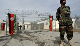 ** FILE ** An Afghan National Army soldier stands in front of the gate of the newly refurbished Pul-e-Charkhy prison during an opening ceremony in Kabul, Afghanistan, in March 2007. (AP Photo/Musadeq Sadeq, File)