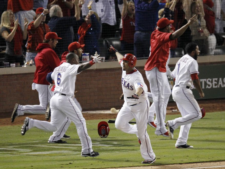 Texas Rangers' Nelson Cruz, center, and teammates celebrate after he hit a grand slam home run in the 11th inning of Game 2 of baseball's American League championship series to beat the Detroit Tigers 7-3, Monday, Oct. 10, 2011, in Arlington, Texas.(AP Photo/Eric Gay)