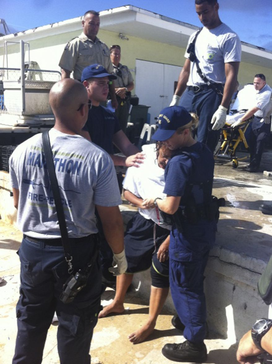 U.S. Coast Guard Seaman Kendra Graves (right) and Petty Officer 3rd Class Robert Femia assist EMS personnel in Marathon, Fla., with one of seven boaters rescued on Sunday, Oct. 9, 2011, after treading water for around 20 hours after their boat capsized and sank. (AP Photo/U.S. Coast Guard)