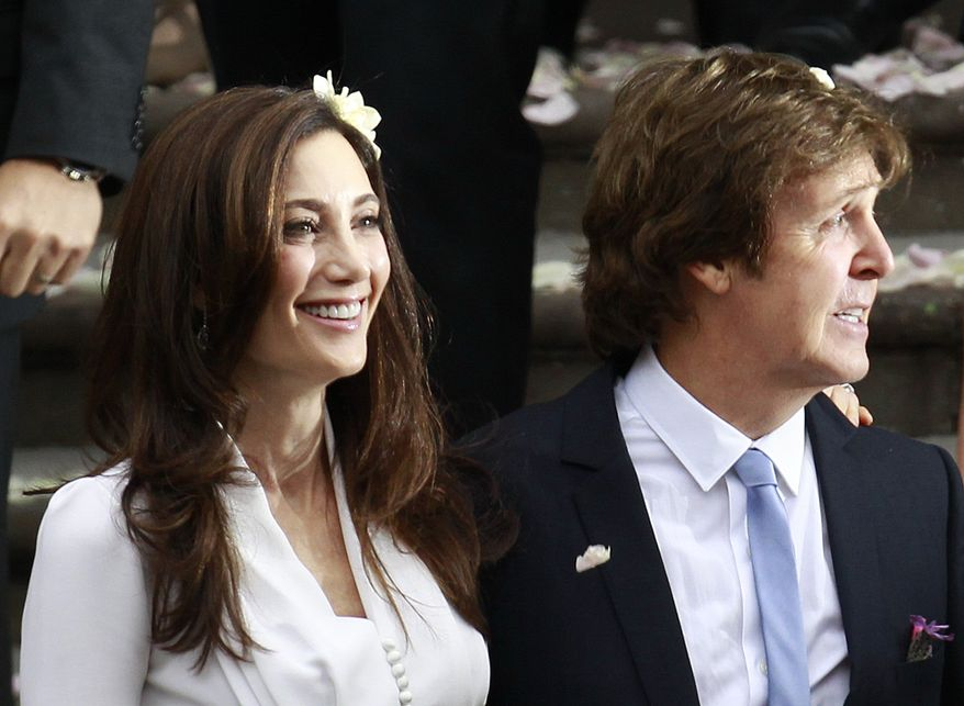 Sir Paul McCartney and his wife, American heiress Nancy Shevell, leave Marylebone Registry Office following their wedding in central London on Oct. 9, 2011. (Associated Press)