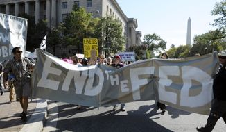 With the Washington Monument behind them, protesters, calling for the end of the Federal Reserve, march Oct. 9, 2011, to the Federal Reserve in Washington. (Associated Press)