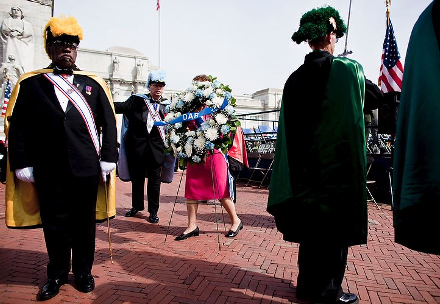 Mary Ann T. Wright (center), president general of the National Society of the Daughters of the American Revolution, presents a wreath before the Columbus Memorial statue during a Columbus Day celebration at Union Station in Washington on Monday, Oct. 10, 2011. (T.J. Kirkpatrick/The Washington Times)