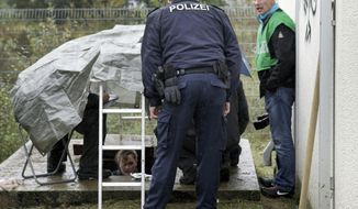 Police officers examine a utility shaft near the rail tracks at the northern exit of the railway tunnel to Berlin's central train station on Monday, Oct. 10, 2011. (AP Photo/Michael Sohn)