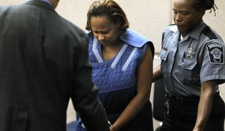 Annette Morales-Rodriguez center, appears in Milwaukee County Intake Court, Monday, Oct. 10, 2011, in Milwaukee. Rodriguez, 33, of Milwaukee, is charged with two counts of homicide in the death of Maritza Ramirez-Cruz, and her unborn son. (AP Photo/Milwaukee Journal-Sentinel, Gary Porter)