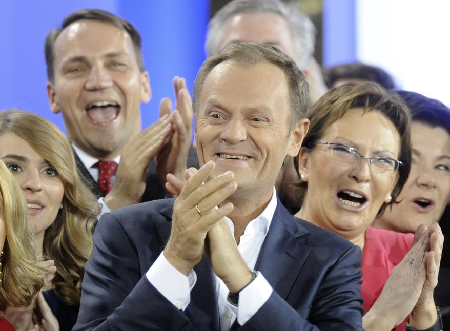 Polish Prime Minister Donald Tusk (center) celebrates in Warsaw with Health Minister Ewa Kopacz (right) and Foreign Minister Radek Sikorski (background left) as the first exit poll is published following parliamentary elections on Sunday, Oct. 9, 2011. (AP Photo/Alik Keplicz)