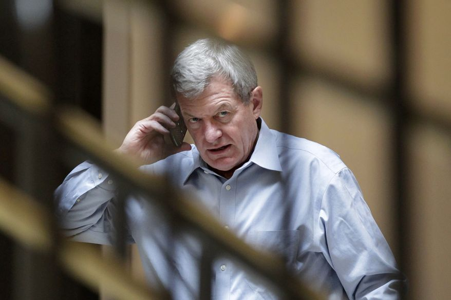 **FILE** Sen. Max Baucus, Montana Democrat and chairman of the Senate Finance Committee, talks on his cell phone Sept. 27, 2011, outside a closed-door meeting of the Joint Select Committee on Deficit Reduction on Capitol Hill. (Associated Press)