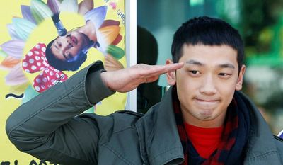 "South Korean pop singer Rain, whose real name is Jung Ji-hoon, gives a military salute to his fans in front of an army training center in Uijeongbu, north of Seoul, on Tuesday. ""Thank you for the 10 years of love,"" Rain, 29, told the hundreds of fans present. (Associated Press)"