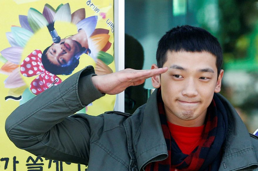 """South Korean pop singer Rain, whose real name is Jung Ji-hoon, gives a military salute to his fans in front of an army training center in Uijeongbu, north of Seoul, on Tuesday. """"Thank you for the 10 years of love,"""" Rain, 29, told the hundreds of fans present. (Associated Press)"""