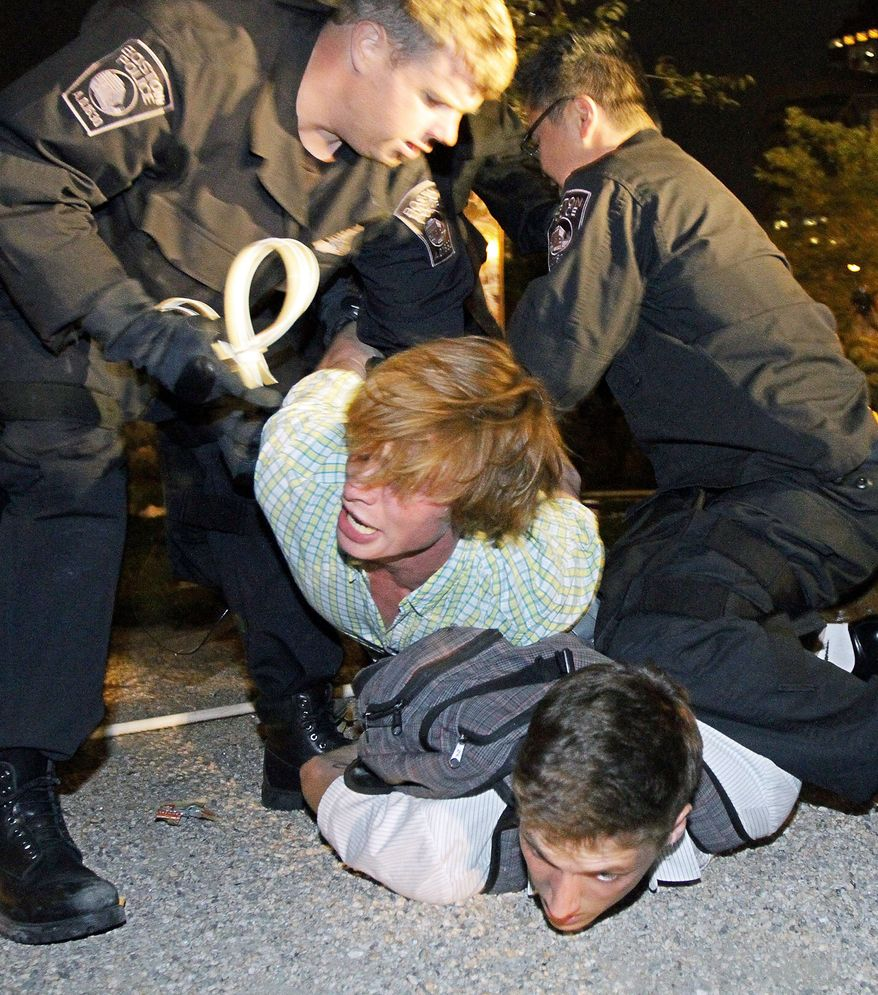 Boston Police officers arrest protesters on Tuesday in a section of the Rose Fitzgerald Kennedy Parkway adjacent to Dewey Square in Boston. (Boston Herald via Associated Press)