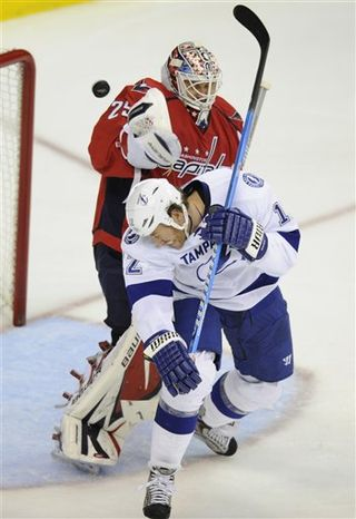 Tampa Bay Lightning left wing Ryan Malone, front, battles for the puck against Washington Capitals goalie Tomas Vokoun, of the Czech Republic, back, during the second period of an NHL hockey game, Monday, Oct. 10, 2011, in Washington. (AP Photo/Nick Wass