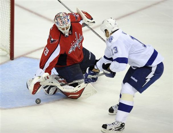 Washington Capitals goalie Tomas Vokoun, (29) of the Czech Republic, reaches for the puck against Tampa Bay Lightning defenseman Pavel Kubina, of the Czech Republic, (13) during the second period of an NHL hockey game, Monday, Oct. 10, 2011, in Washington. (AP Photo/Nick Wass)