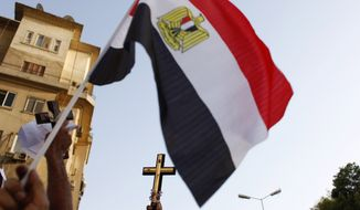 Egyptian Coptic demonstrators carry Christian crosses and an Egyptian flag during a Copts demonstration that developed into clashes with army soldiers in Cairo on Oct. 9, 2011. (Associated Press)