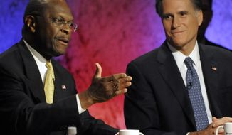 Republican presidential candidate Herman Cain speaks Tuesday night as former Massachusetts Gov. Mitt Romney listens during a GOP debate at Dartmouth College in Hanover, N.H. (Associated Press)