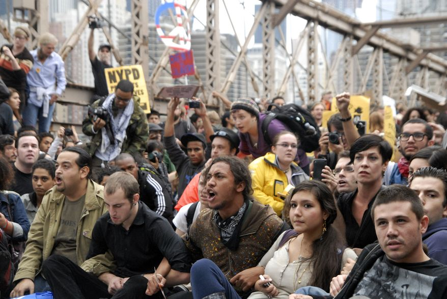 **FILE** Protesters sit with arms linked on New York's Brooklyn Bridge on Oct. 1, 2011, before police began making arrests during a march by Occupy Wall Street. (Associated Press)