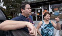 Jose Contreras and his wife, Nelva, discuss their reasons for closing their Hispanic store and restaurant (rear) in Albertville, Ala., on Wednesday, Oct. 12, 2011. (AP Photo/Dave Martin)