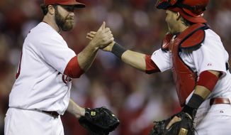 St. Louis Cardinals relief pitcher Jason Motte celebrates with catcher Yadier Molina after the final out in the ninth inning of Game 3 of baseball's National League championship series against the Milwaukee Brewers Wednesday, Oct. 12, 2011, in St. Louis. The Cardinals won 4-3 to take a 2-1 lead in the series. (AP Photo/Matt Slocum)