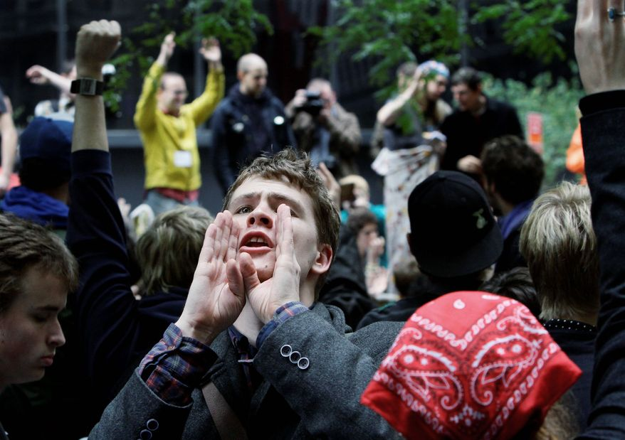 Lucas Brinson, 21, from Davis, Calif, relays information to others at the Occupy Wall Street encampment in Zuccotti Park in New York. The occupants have been told by the park's owners that they can return after the park is cleaned Friday if certain rules are followed. (Associated Press)