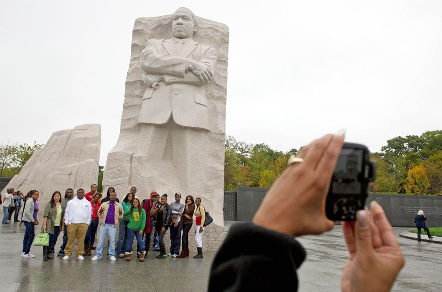 Dawn Covington takes a group photo of students from the Career Academy in Baltimore on Thursday as they gather around the Martin Luther King, Jr. National Memorial on the Mall. Hurricane Irene in August forced postponement of its dedication, which will take place on Sunday. (Rod Lamkey Jr./The Washington Times)