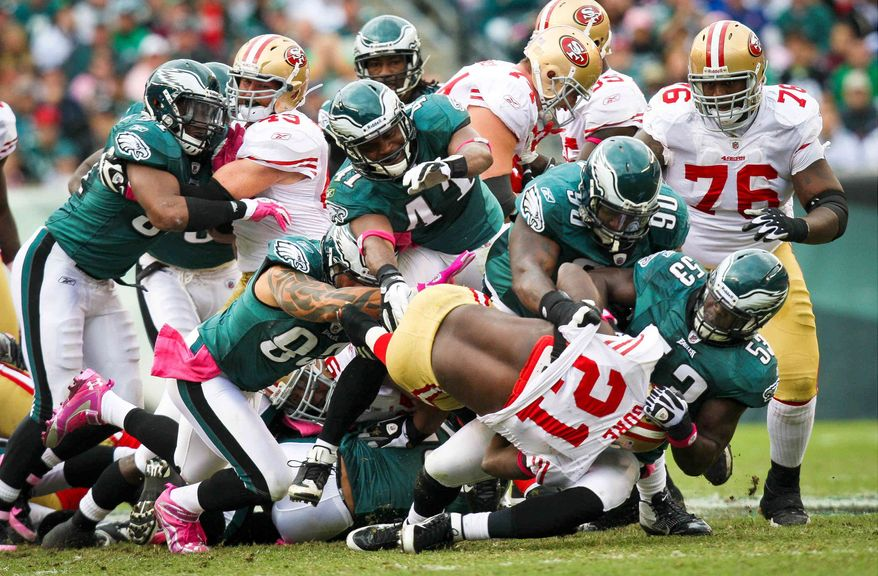San Francisco 49ers running back Frank Gore is brought down by a wall of Philadelphia Eagles defenders during an NFL football game Sunday, Oct. 2, 2011, in Philadelphia. (AP Photo/The News-Journal, Suchat Pederson) NO SALES