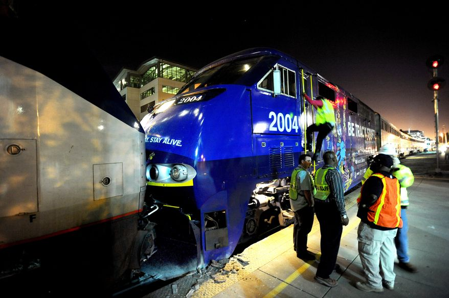 Two Amtrak locomotives rest against each other after colliding at an Oakland, Calif., station on Wednesday, Oct. 12, 2011. (AP Photo/Noah Berger)
