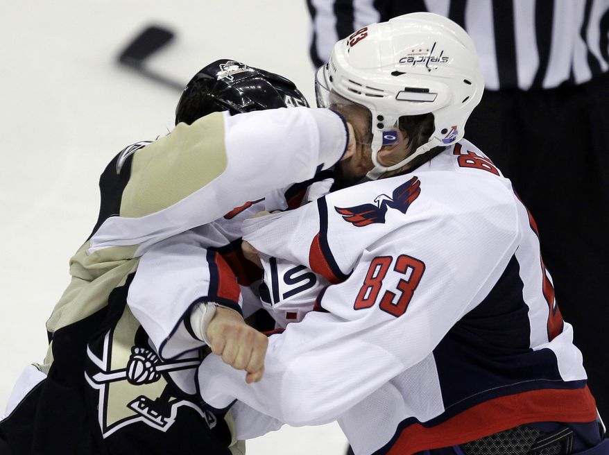 Pittsburgh Penguins' Arron Asham lands a punch to the face of Washington Capitals' Jay Beagle (83) during a third-period fight. Beagle left the game after the fight as the Caps won in OT, 3-2. (Associated Press)
