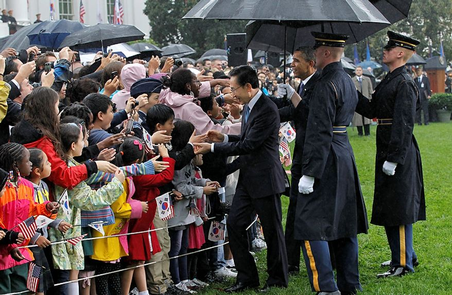President Obama and South Korean President Lee Myung-bak are welcomed by local schoolchildren during a rainy state arrival ceremony on Thursday, Oct. 13, 2011, on the South Lawn of the White House in Washington.  (AP Photo/J. Scott Applewhite)