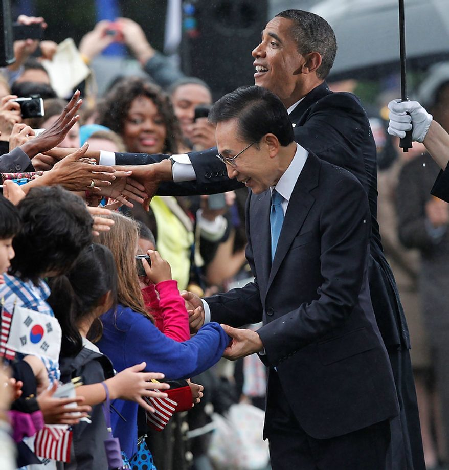 President Barack Obama and South Korean President Lee Myung-bak are welcomed by local school children during a rainy state arrival ceremony,  Thursday, Oct. 13, 2011, on the South Lawn of the White House in Washington.  (AP Photo/J. Scott Applewhite)