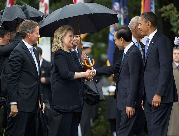 Secretary of State Hillary Clinton shakes hands with South Korean President Lee Myung-bak, accompanied by President Barack Obama, during a state arrival ceremony on the South Lawn of the White House in Washington, Thursday, Oct. 13, 2011.  At left is Treasury Secretary Timothy Geithner.  (AP Photo/Evan Vucci)