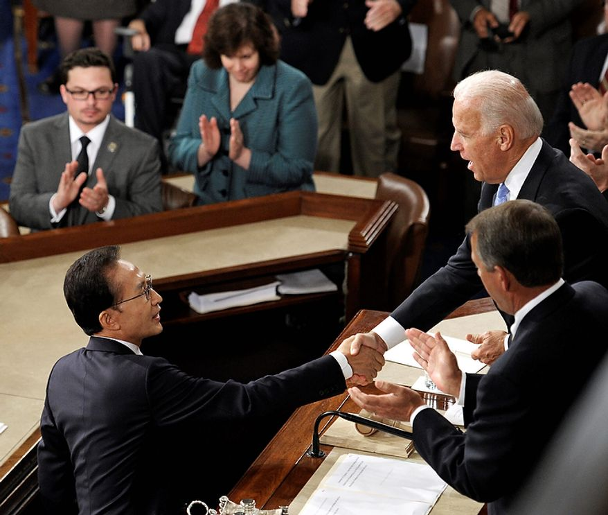South Korean President Lee Myung-bak, left, shakes hands with Vice President Joe Biden after addressing a joint session of Congress at the Capitol, in Washington, Thursday, Oct. 13, 2011. (AP Photo/Cliff Owen)