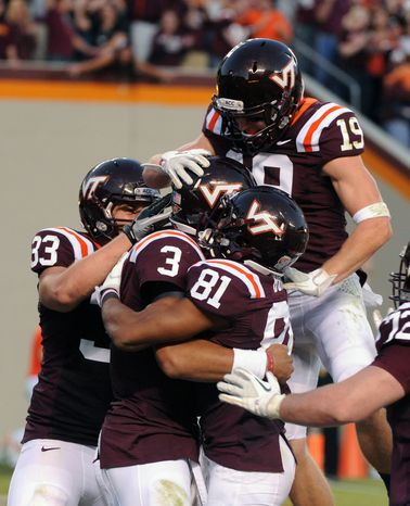 Virginia Tech's Logan Thomas (3) is mobbed by teammates Jarett Boykin (81), Chris Drager (33) and Danny Coale (19) after scoring the game-winning touchdown against Miami Saturday, Oct. 8, 2011, in Blacksburg, Va. Virginia Tech defeated Miami 38-35. (AP Photo/Don Petersen)