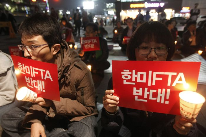 """South Korean protesters stage a rally against a free trade agreement between South Korea and the United States in Seoul on Oct. 13, 2011. The letters on the signs read """"Opposed FTA between South Korea and the United States."""" (Associated Press)"""