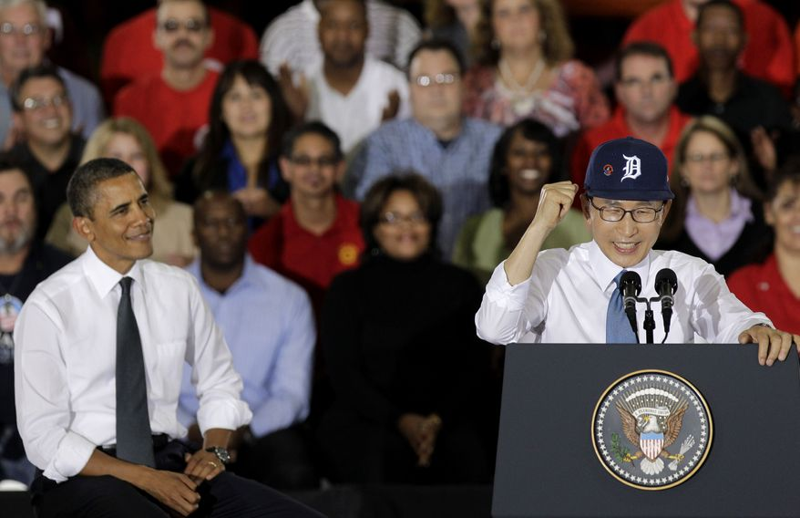 President Obama (left) listens as South Korean President Lee Myung-bak, wearing a Detroit Tigers baseball cap, speaks at the General Motors Orion assembly plant in Orion Township, Mich., on Oct. 14, 2011. (Associated Press)
