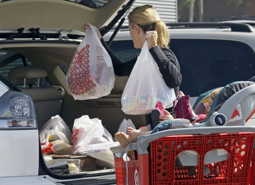 **FILE** A woman with a child loads purchases from a Target store into her car Sept. 29, 2011, in Culver City, Calif. (Associated Press)