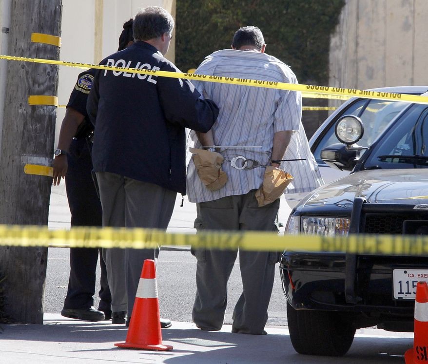 Police officers lead Scott Evans Dekraai to a patrol car after arresting him following a shooting at the nearby Salon Meritage that left eight people dead and one critically injured in Seal Beach, Calif., Wednesday, Oct. 12, 2011. (AP Photo/Reed Saxon)