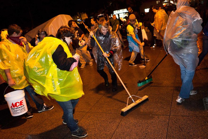 Demonstrators affiliated with the Occupy Wall Street protests sweep Zucotti Park to preempt a scheduled cleanup by owners Friday morning that protestors say is a move to shut them down, Friday, Oct. 14, 2011, in New York. (AP Photo/John Minchillo)